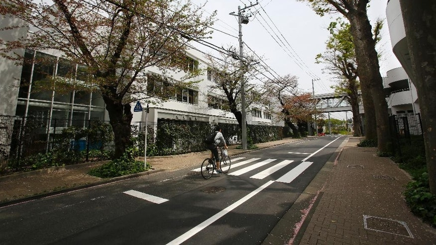 In this Sunday, April 10, 2016, photo, a man rides a bicycle past St. Mary's International School in Tokyo. The Roman Catholic Church's worldwide sex abuse scandal has stretched into one of the world's least Catholic countries: Japan. Former students at a prestigious all-boys parochial school allege they were molested or raped by religious brothers who taught there decades ago. One former student says he was raped in the chapel by two brothers when he was 11. (AP Photo/Shizuo Kambayashi)