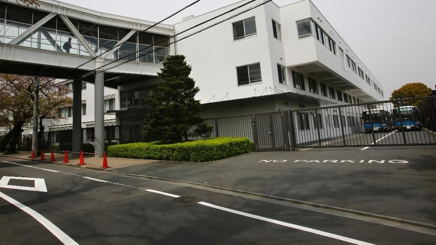 In this Sunday, April 10, 2016, photo, a man walks on a connecting bridge of St. Mary's International School as its school buses are parked in its compound in Tokyo. The Roman Catholic Church's worldwide sex abuse scandal has stretched into one of the world's least Catholic countries: Japan. Former students at a prestigious all-boys parochial school allege they were molested or raped by religious brothers who taught there decades ago. One former student says he was raped in the chapel by two brothers when he was 11. (AP Photo/Shizuo Kambayashi)