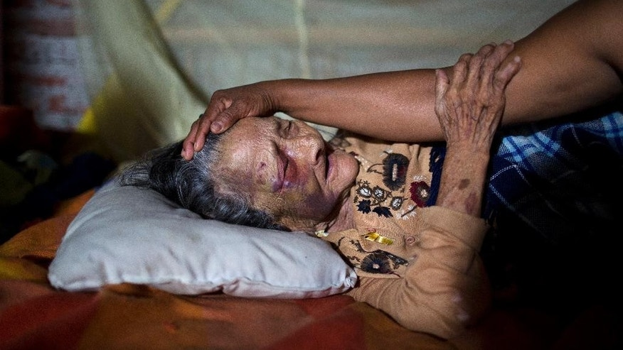 Maria Victoria, 89, is comforted by her daughter Mariana in Estancia Las Palmas, Ecuador, Tuesday, April 19, 2016. Maria Victoria was injured when a column fell on her after 7.8-magnitude earthquake collapsed her home. The strongest earthquake to hit Ecuador in decades flattened buildings and buckled highways along its Pacific coast, sending the Andean nation into a state of emergency. (AP Photo/Rodrigo Abd)