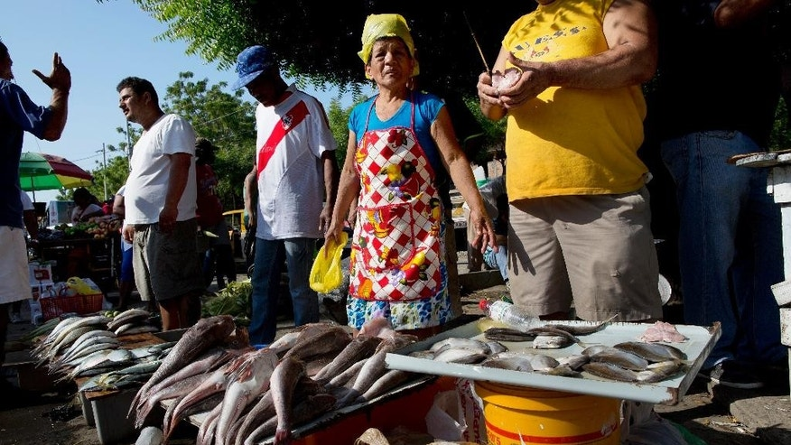 Vendors sell fish in a makeshift market, set up near the business district which was severely damaged by a 7.8-magnitude earthquake, in Manta, Ecuador, Wednesday, April 20, 2016. Businesses are slowly opening, although electricity and running water are still scarce in the Pacific coastal city. (AP Photo/Rodrigo Abd)