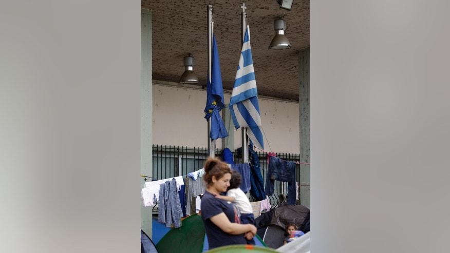 """The EU, left, and Greek flags tied together tower over migrants and refugees gathered at  a railway station at the northern Greek border point of Idomeni, Greece, Wednesday, April 20, 2016. Human Rights Watch says the initial round of deportations of migrants from Greece to Turkey under a new European Union-Turkey deal were """"rushed, chaotic and violated the rights of those deported."""" (AP Photo/Gregorio Borgia)"""