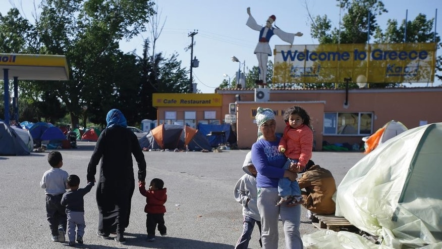 """Migrants and refugees gather at a gas station turned into a makeshift camp at the northern Greek border point of Idomeni, Greece, Wednesday, April 20, 2016. Human Rights Watch says the initial round of deportations of migrants from Greece to Turkey under a new European Union-Turkey deal were """"rushed, chaotic and violated the rights of those deported."""" (AP Photo/Gregorio Borgia)"""