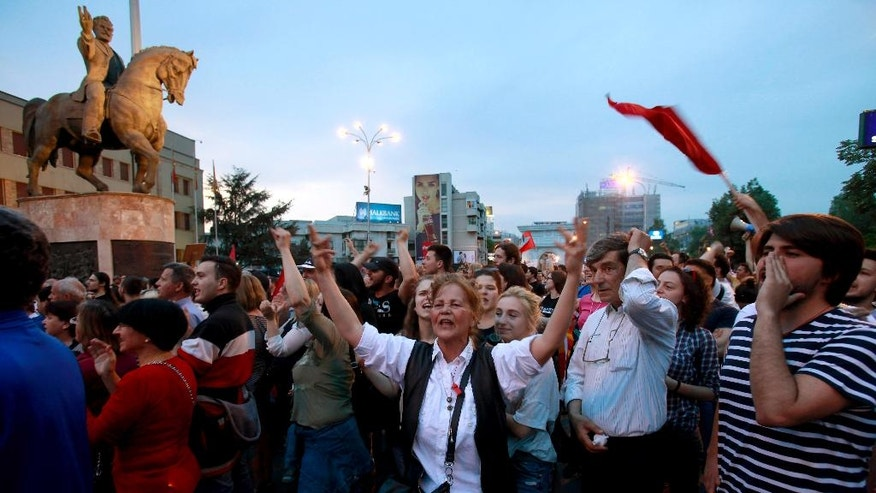 """FILE - This is a  Monday, April 18, 2016  file photo of protestors chant """"No justice, no peace"""" while marching in front of the parliament building in Skopje, Macedonia. Thousands of people have been protesting almost nightly in the Macedonian capital, Skopje, since President Gjorge Ivanov announced a decision last week to grant presidential pardons that halted criminal proceedings against dozens of people, including high-ranking politicians, accused in a wiretapping scandal that has roiled Macedonia for months. (AP Photo/Boris Grdanoski, File)"""