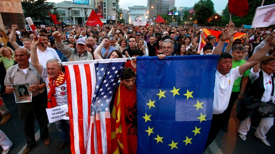 """FILE - This is a  Monday, April 18, 2016  file photo  a protestor holds the flags of the United States, left, and the European Union, right, while others chant """"No justice, no peace"""" during a march in front of the parliament building in Skopje, Macedonia. Thousands of people have been protesting almost nightly in the Macedonian capital, Skopje, since President Gjorge Ivanov announced a decision last week to grant presidential pardons that halted criminal proceedings against dozens of people, including high-ranking politicians, accused in a wiretapping scandal that has roiled Macedonia for months. (AP Photo/Boris Grdanoski, File)"""