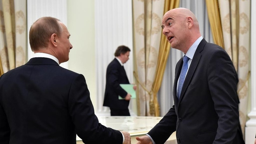 Russian President Vladimir Putin, left, shakes hands with FIFA President Gianni Infantino during their meeting in the Kremlin in Moscow, Wednesday, April 20, 2016. (Alexander Nemenov/Pool Photo via AP)