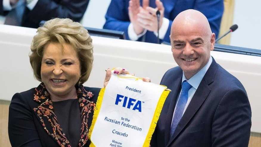 FIFA President Gianni Infantino, right, presents a FIFA pennant to Federation Council Speaker Valentina Matviyenko, after Infantino addressed the upper chamber of the Russian parliament in Moscow, Russia, Wednesday, April 20, 2016. (AP Photo/Alexander Zemlianichenko)
