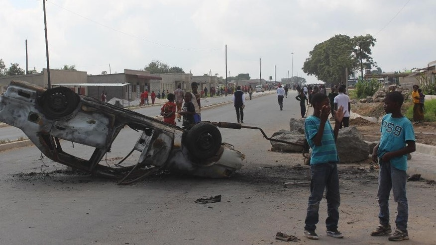 In this photo taken Thursday, April 7 2016 a burnt out vehicle lays on it's roof in Lusaka, Zambia. On Wednesday April 20, 2016 police arrested over 250 people for alledgedly attacking Rwandan nationals and looting their stores in violence that police said killed two people in ritual killings that started in March. (AP Photo/Moses Mwape)