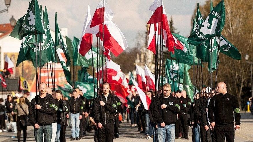 In this photo taken on April 16, 2016, members of extreme-right National-Radical Camp march with national white-and-red flags and their organization's green flags in the eastern city of Bialystok to mark 82 years of the organization that was founded on fascist ideas and promoted antisemitism before World War II. Catholic Church authorities in eastern Poland denounced nationalist views Wednesday, April 20, 2016 and apologized after the radical extreme-right organization held a Mass in the regional cathedral. (AP Photo/Michal Kosc )