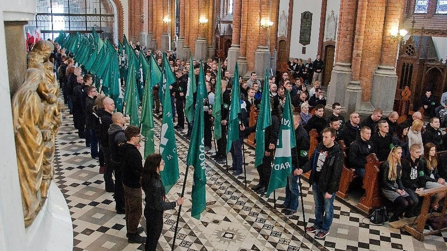 In this photo taken on April 16, 2016, members of extreme-right National-Radical Camp with their organization's green flags line the aisle at the Catholic Cathedral in the eastern city of Bialystok, where a Mass marked 82 years of the organization that was founded on fascist ideas and promoted antisemitism before World War II. Catholic Church authorities in eastern Poland denounced nationalist views Wednesday, April 20, 2016 and apologized after the radical extreme-right organization held a Mass in the regional cathedral. (AP Photo/Michal Kosc )