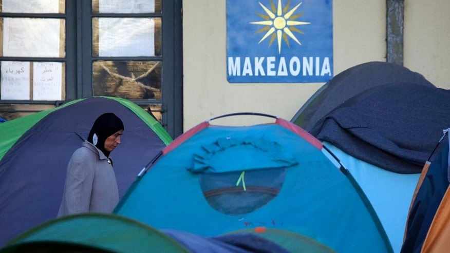 "A woman walks through tents and a sign that reads: ""Greece-Macedonia"" at a railway station turned into a migrants and refugees makeshift camp at the northern Greek border point of Idomeni, Greece, Wednesday, April 20, 2016. Human Rights Watch says the initial round of deportations of migrants from Greece to Turkey under a new European Union-Turkey deal were ""rushed, chaotic and violated the rights of those deported."" (AP Photo/Gregorio Borgia)"