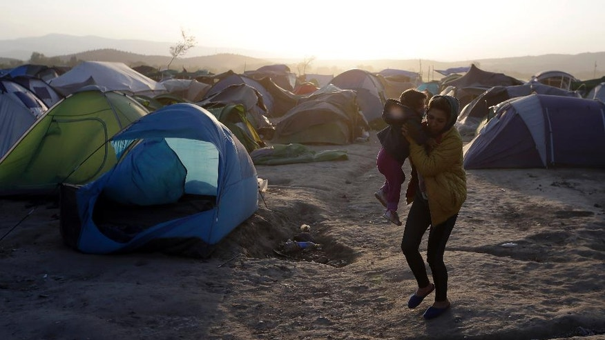 "A woman holds her baby as she walks by a tent blown by a strong wind at a camp for migrants and refugees at the northern Greek border point of Idomeni, Greece, Wednesday, April 20, 2016. Human Rights Watch says the initial round of deportations of migrants from Greece to Turkey under a new European Union-Turkey deal were ""rushed, chaotic and violated the rights of those deported."" (AP Photo/Gregorio Borgia)"
