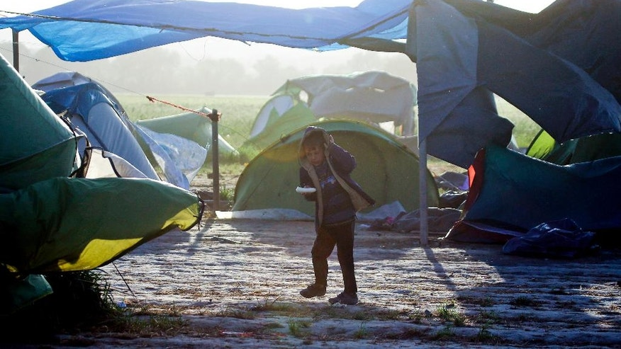 "A child walks through tents blown by a strong wind at a makeshift camp for migrants and refugees at the northern Greek border point of Idomeni, Greece, Wednesday, April 20, 2016. Human Rights Watch says the initial round of deportations of migrants from Greece to Turkey under a new European Union-Turkey deal were ""rushed, chaotic and violated the rights of those deported."" (AP Photo/Gregorio Borgia)"