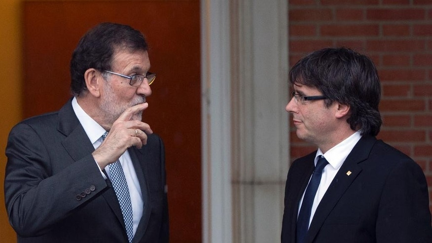 Spain's acting Prime Minister Mariano Rajoy, left, speaks with Catalan regional President Carles Puigdemont at the Moncloa Palace in Madrid, Spain, Wednesday, April 20, 2016. Rajoy held his first official meeting with Catalonia's pro-independence regional president, Carles Puigdemont, with talks likely to center on the region's finances although the secession issue is certain to surface. The independence drive has gathered force in recent years after Catalonia failed to win more financing concessions from Madrid. (AP Photo/Paul White)