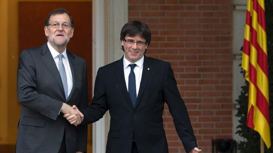Spain's acting Prime Minister Mariano Rajoy, left, shakes hands with Catalan regional President Carles Puigdemont at the Moncloa Palace in Madrid, Spain, Wednesday, April 20, 2016. Rajoy held his first official meeting with Catalonia's pro-independence regional president, Carles Puigdemont, with talks likely to center on the region's finances although the secession issue is certain to surface. The independence drive has gathered force in recent years after Catalonia failed to win more financing concessions from Madrid. (AP Photo/Paul White)