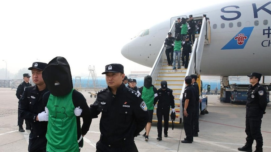 FILE - In this file photo taken April 13, 2016, and released by Xinhua News Agency, Chinese and Taiwanese suspects involved in wire fraud are escorted off a plane upon arriving at the Beijing Capital International Airport in Beijing, China. A 10-member delegation from Taiwan of judicial and police officials arrived in Beijing on Wednesday seeking to ensure fair treatment for their nationals who were deported from Kenya to face wire fraud charges in China, a case that has prompted concerns that Beijing is bringing additional diplomatic pressure on the island it considers its own territory. (Yin Gang/Xinhua News Agency via AP, File) NO SALES