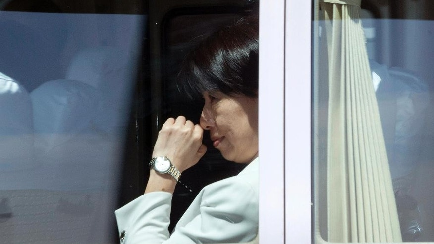 Chen Wen-chi, Taiwan's head of the Justice Ministry's department of International and cross-straits legal affairs sits in a coaster as it leave from the VIP exit of the airport in Beijing, China, Wednesday, April 20, 2016. Taiwanese officials are seeking to ensure fair treatment for their nationals who were deported from Kenya to face wire fraud charges in China, a case that has prompted concerns that Beijing is bringing additional diplomatic pressure on the island it considers its own territory. (AP Photo/Ng Han Guan)