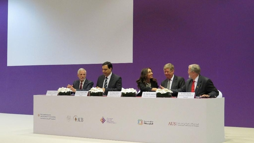CEO of the Arab Youth Fund Maysa Jalbout, center, shakes hands with representatives of four top universities in the Middle East after signing agreements in Dubai, United Arab Emirates on Wednesday, April 20, 2016. A multibillionaire businessman from the United Arab Emirates has launched the Arab world's largest education fund, setting aside $1.14 billion (4.2 billion dirhams) in grants for underserved youth from the region. (AP Photo/Aya Batrawy)