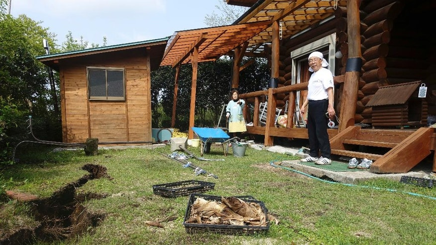 In this April 19, 2016 photo, Koji Fuchigami and his wife Yachiyo look at the damage on the ground as they briefly return home to pick up valuables and fresh clothes to take to their shelter in Minamiaso, Kumamoto prefecture, Japan. A mountain village that attracted retirees, tourists and agriculture students to a college campus faces a grim future after last week's devastating earthquake. (AP Photo/Mari Yamaguchi)