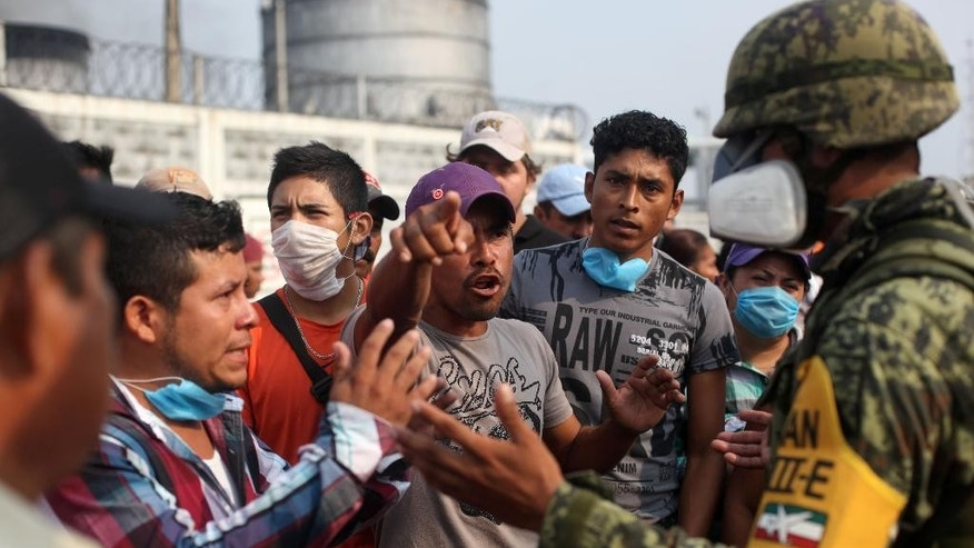 A relative of a missing worker argues with a Mexican army soldier as he demands to be allowed to get more information, outside the Pajaritos petrochemical complex in Coatzacoalcos, Mexico, Thursday, April,  21, 2016. At least 13 people are now confirmed dead and scores of others were injured in a Wednesday afternoon explosion inside the plant. The state oil company Petroleos Mexicanos, or Pemex, said the plant, operated by Mexichem, in partnership with Pemex, produces vinyl chloride, a hazardous industrial chemical. (AP Photo/Felix Marquez)