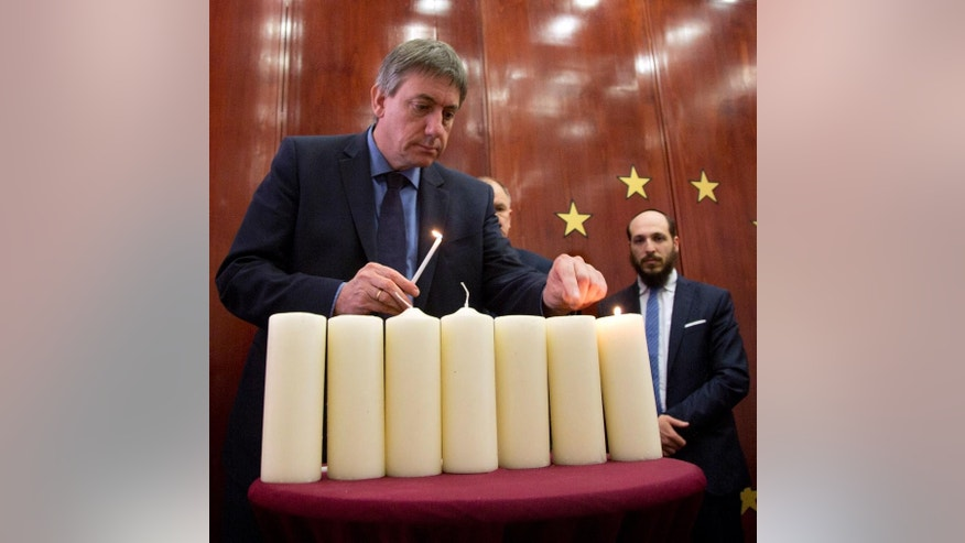 Belgium's Interior Minister Jan Jambon, left, prepares to light a candle with other leaders of various faiths during a remembrance service for victims of the Brussels attacks at the Jewish Center of Brussels on Tuesday, April 19, 2016. Leaders of various faiths and a school group from the Molenbeek district of Brussels attended the service to remember victims who died or where injured during attacks at the Brussels airport and metro station on March 22, 2016. (AP Photo/Virginia Mayo)