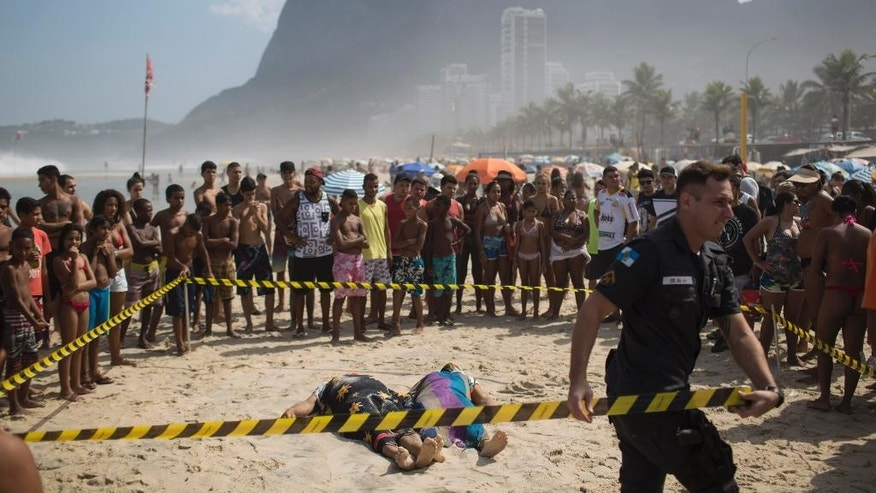 A police officer tapes off the area around two people who were killed when a bike lane collapsed in Rio de Janeiro, Brazil, Thursday, April 21, 2016. Part of an elevated bike lane built ahead of the Olympic Games collapsed on Thursday, killing at least two people who were on it when cement gave way and crashed onto the beach below. (AP Photo/Felipe Dana)