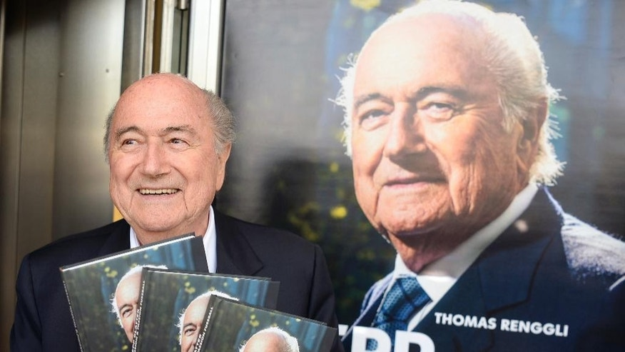 "Former FIFA president Sepp Blatter poses with copies of the book ""Sepp Blatter: Mission and Passion Football"", during the book presentation in Zurich, Switzerland, Thursday, April 21, 2016. The book was written by his official spokesman Thomas Renggli. (Walter Bieri/Keystone via AP)"