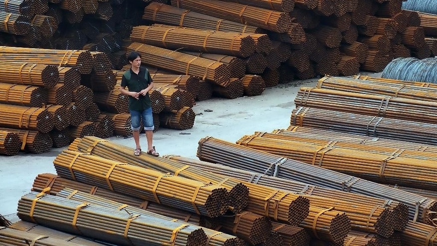 In this Aug. 22, 2014 photo, a man stands on bundles of steel pipes in a steel products dockyard along the Yangtze River in southwestern China's Chongqing Municipality. Regulators told Chinese banks on Thursday, April 21, 2016, to finance steel exports to help reduce a supply glut in a move that could worsen trade tensions with Europe and the United States. (Chinatopix via AP) CHINA OUT