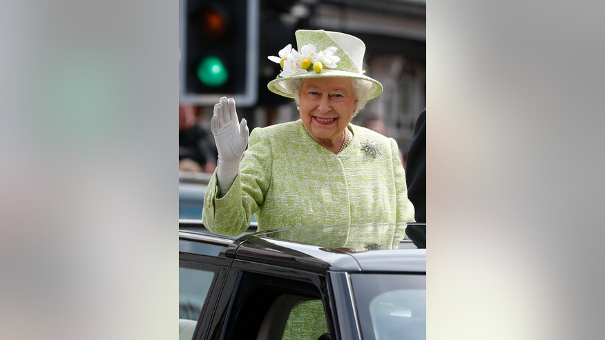 Britain's Queen Elizabeth II waves to the crowd as she rides in an open top car with Prince Phillip to celebrate her 90th birthday in Windsor, England, Thursday April 21, 2016. The queen was born Princess Elizabeth on April 21, 1926, and became queen at 25 upon the death of her father, King George VI, in 1952. A majority of Britons have lived under no other monarch. (AP Photo/Alastair Grant)
