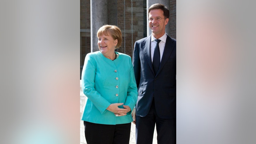 German Chancellor Angela Merkel, left, poses with Dutch Prime Minister Mark Rutte as she arrives for the ceremony of the Four Freedoms Award in Middelburg, Netherlands, Thursday, April 21, 2016. (AP Photo/Peter Dejong)