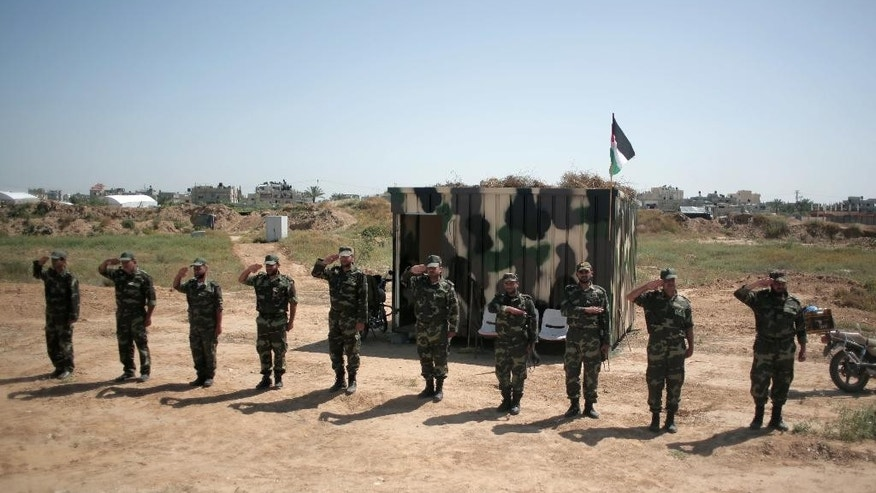 Palestinian Hamas security forces stand in formation on the Palestinian side of the border with Egypt in Rafah, southern Gaza Strip, Thursday, April 21, 2016. Hamas has deployed forces along the Egyptian-Gaza border to counter Cairo's concerns it is aiding militants from the Islamic State group in Egypt's lawless Sinai Peninsula. (AP Photo/ Khalil Hamra)