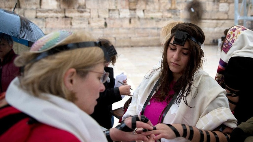 "FILE - In this Sunday, Feb. 7, 2016 file photo, Israeli women put on Tefillin also known as Phylacteries, a small leather box containing religious text usually worn by Jewish men, at the Western Wall, the holiest site where Jews can pray in Jerusalem's Old City. Israel's attorney general has banned Jewish women's prayer group called Women of the Wall from holding an all-female ""priestly blessing"" next week and it is an unrecognized custom that has never been held at the Western Wall. (AP Photo/Sebastian Scheiner, File)"