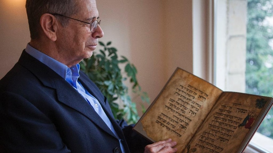 In this photo taken Wednesday, April 13, 2016, Eli Barzilai holds a copy of the Birds' Head Haggadah in his house in Jerusalem. The Barzilai family, the grandchildren of one of the earliest Jewish victims of the Nazis, are laying claim to a jewel of Israel's leading museum: the world's oldest surviving illustrated Passover manuscript. The descendants of a German Jewish lawmaker say the famed Birds' Head Haggadah, a medieval copy of the text read around Jewish dinner tables on Passover, was stolen from their family during the Nazi era and sold without their consent to the predecessor of the Israel Museum in Jerusalem 70 years ago. (AP Photo/Dan Balilty)
