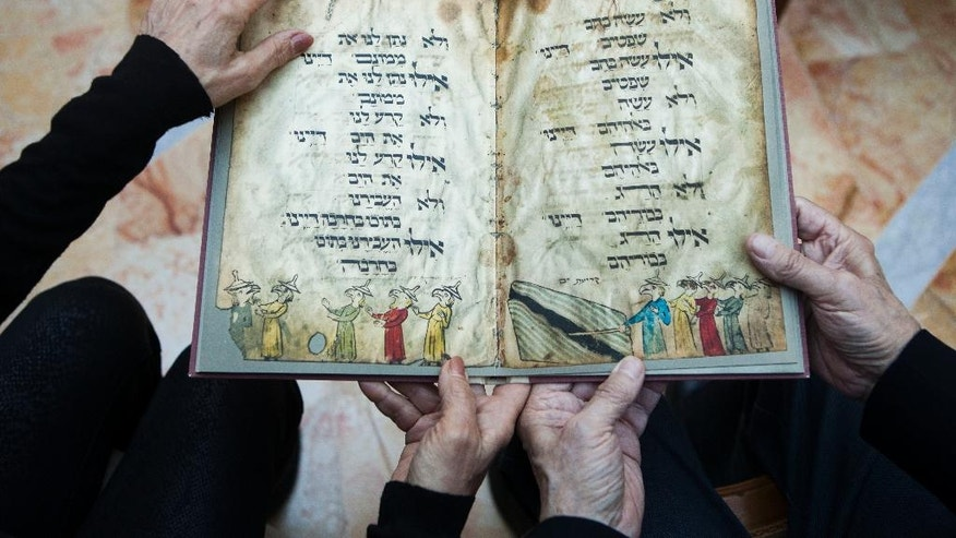 In this photo taken Wednesday, April 13, 2016, Eli and Shuli Barzilai holds a copy of the Birds' Head Haggadah in his house in Jerusalem. The Barzilai family grandchildren of one of the earliest Jewish victims of the Nazis are laying claim to a jewel of Israel's leading museum: the world's oldest surviving illustrated Passover manuscript. The descendants of a German Jewish lawmaker say the famed Birds' Head Haggadah, a medieval copy of the text read around Jewish dinner tables on Passover, was stolen from their family during the Nazi era and sold without their consent to the predecessor of the Israel Museum in Jerusalem 70 years ago. (AP Photo/Dan Balilty)