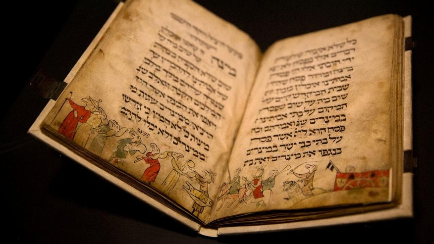 In this photo taken Wednesday, April 20, 2016, the famed Birds' Head Haggadah, a medieval copy of a text read around the Passover holiday table, is seen on display at the Israel Museum in Jerusalem. The grandchildren of one of the earliest Jewish victims of the Nazis are laying claim to a jewel of Israel's top museum: the world's oldest surviving illustrated Passover manuscript. (AP Photo/Sebastian Scheiner)