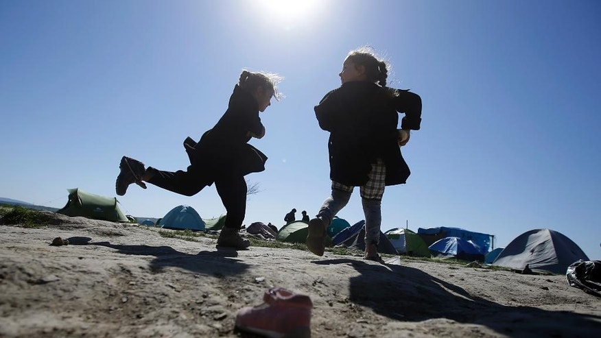 Children play in a makeshift camp at the northern Greek border point of Idomeni, Greece, Thursday, April 21, 2016. Many thousands of migrants remain at the Greek border with Macedonia, hoping that the border crossing will reopen, allowing them to move north into central Europe. (AP Photo/Gregorio Borgia)