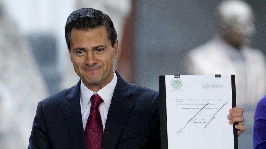 Mexican President Enrique Pena Nieto holds up a signed document during an announcement on proposed marijuana policy, in Mexico City, Thursday April 21, 2016. Pena Nieto said Thursday he will ask Congress to raise the limit on decriminalized marijuana for personal use to 28 grams, or about one ounce. Mexico had previously exempted from prosecution only five grams, or less than a fifth of an ounce. The bill presented would free people who are on trial or serving time for possession of up to an ounce of marijuana. (AP Photo/Eduardo Verdugo)