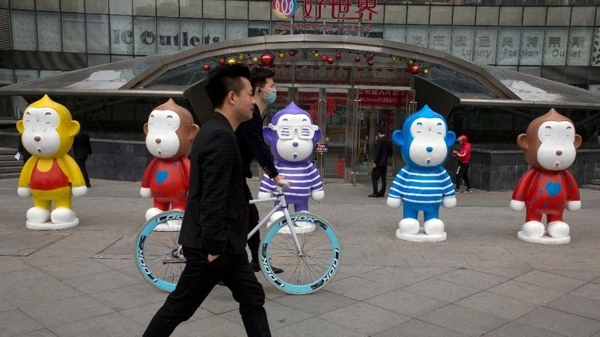 In this Tuesday, April 19, 2016 photo, men past by colorful monkey sculptures displayed outside a shopping mall in Beijing China is increasingly becoming a nation of town and city dwellers, with more than 55 percent now living in urban areas, the government said Thursday, April 21, 2016. (AP Photo/Ng Han Guan)