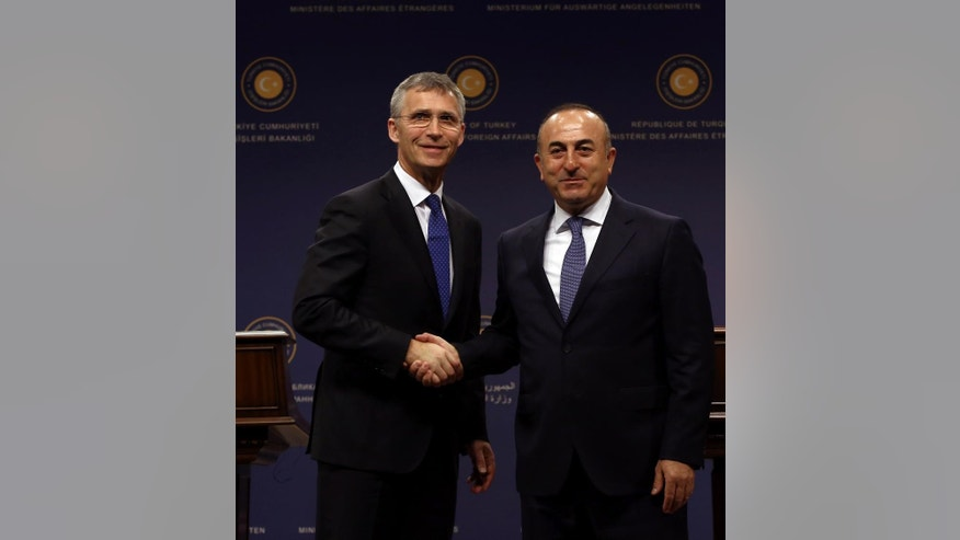 NATO Secretary General Jens Stoltenberg, left, and Turkish Foreign Minister Mevlut Cavusoglu shake hands after a joint news conference in Ankara, Turkey, Thursday, April 21, 2016. Stoltenberg says efforts to stem the tide of migrants seeking the shores of Europe are working.(AP Photo/Burhan Ozbilici)