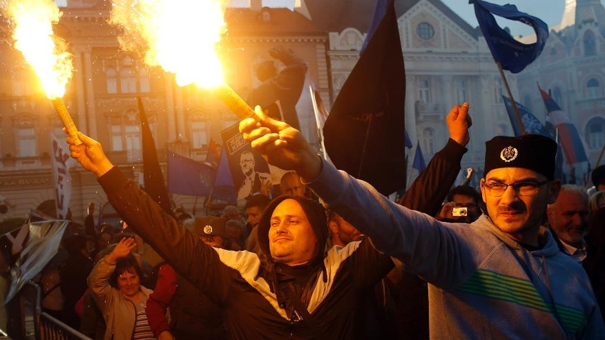Serbian Radical Party supporters light torches during a pre-election rally in Novi Sad, Serbia, Wednesday, April 20, 2016. Serbian voters go to the polls on Sunday in a snap election that will test Prime Minister Aleksandar Vucic's proclaimed bid to lead the Balkan country toward European Union integration. (AP Photo/Darko Vojinovic)