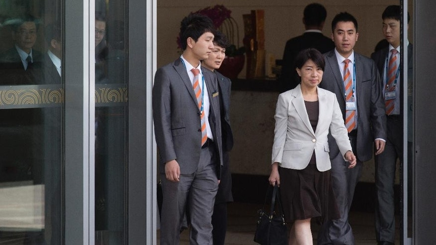 FILE - In this April 20, 2016 file photo, Chen Wen-chi, center, Taiwan's head of the Justice Ministry's department of International and cross-straits legal affairs, walks out of the VIP exit of the airport in Beijing, China.  All 45 Taiwanese wire fraud suspects detained in Beijing after being deported from Kenya have confessed to their crimes and will be put on trial, a Chinese police official was quoted on Friday, April 22, 2016,  as saying, signaling a refusal to compromise on a case that has raised new frictions between Taiwan and China.  (AP Photo/Ng Han Guan, File)