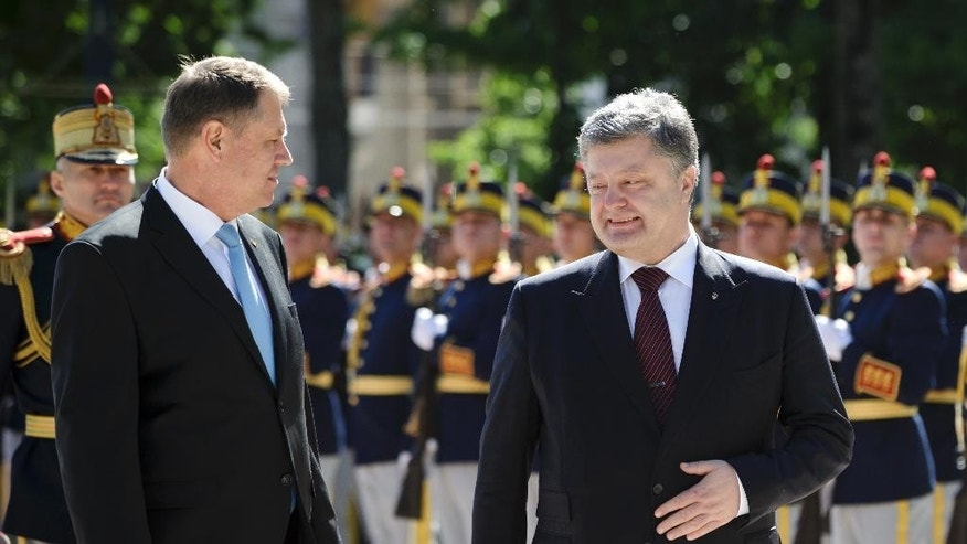 Ukraine's President Petro Poroshenko, right, walks with Romanian President Klaus Iohannis by an honor guard during the welcoming ceremony at the Cotroceni Palace in Bucharest, Romania, Thursday, April 21, 2016. Poroshenko said sanctions on Russia must stay in place as long as hostilities in eastern Ukraine continue during talks that focused on security with his Romanian counterpart Iohannis. (AP Photo/Vadim Ghirda)