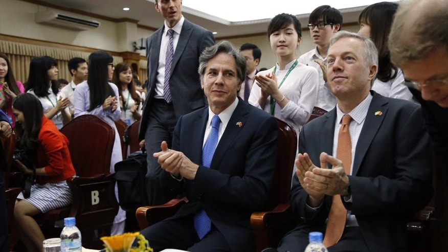 U.S. Deputy Secretary of State Antony Blinken, center, claps with U.S. Ambassador to Vietnam Ted Osius, second from right, during his visit to Vietnam National University in Hanoi, Vietnam, Thursday, April, 21, 2016. Blinken on Thursday questioned China's intentions with its massive land reclamation project in the South China Sea during his visit. China claims the entire South China sea, a water area believed to be rich in oil and gas and is one of the world's busiest maritime lines. The territorial claim is disputed by other countries in the region, including Vietnam and the Philippines. (AP Photo/Tran Van Minh)
