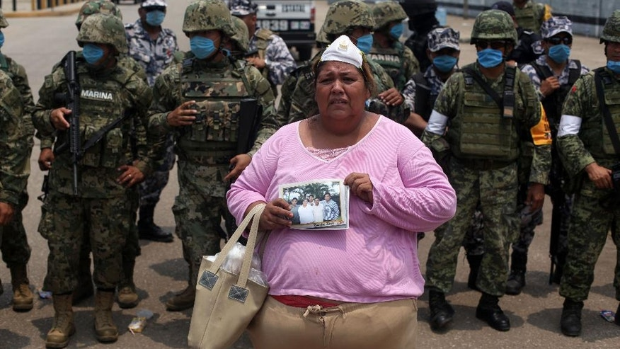 Rosa Villalobos stands in front of army soldiers as she holds up a photo of her son, Luis Alfonso Ruiz, 25, (on the right of the photo), as she tries to get information on his whereabouts outside one of the main entrances to the Pajaritos petrochemical complex in the city of Coatzacoalcos, Mexico, Thursday, April,  21, 2016. Ruiz is one of several workers still unaccounted for while at least 13 people are now confirmed dead and scores of others have been injured in an explosion inside this plant. The state oil company, Petroleos Mexicanos, or Pemex, said explosion occurred in a plant that produces vinyl chloride, a hazardous industrial chemical. (AP Photo/Felix Marquez)