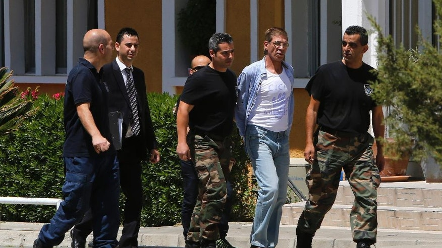 "EgyptAir plane hijack suspect Seif Eddin Mustafa, 59, 2nd right, with t-shirt  is escorted by Cyprus police officers as he arrives in a court in capital Nicosia, Cyprus, Friday, April 22, 2016. Mustafa described as ""psychologically unstable"" hijacked a flight on  Tuesday, March 29, 2016, from Egypt to Cyprus and threatened to blow it up. His explosives turned out to be fake, and he surrendered with all passengers released unharmed after a bizarre six-hour standoff. (AP Photo/Petros Karadjias)"