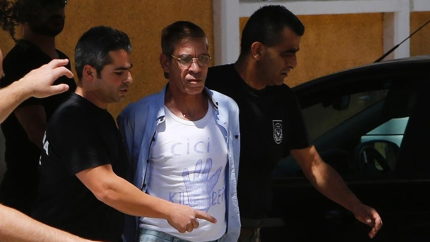 "EgyptAir plane hijack suspect Seif Eddin Mustafa, 59, center with t-shirt  is escorted by Cyprus police officers as he arrives in a court in capital Nicosia, Cyprus, Friday, April 22, 2016. Mustafa described as ""psychologically unstable"" hijacked a flight on  Tuesday, March 29, 2016, from Egypt to Cyprus and threatened to blow it up. His explosives turned out to be fake, and he surrendered with all passengers released unharmed after a bizarre six-hour standoff. (AP Photo/Petros Karadjias)"