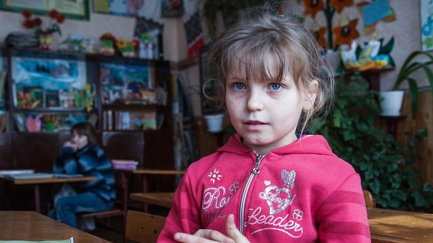 In this photo taken on Tuesday, April  5, 2016, Olesya Petrova, 9, attends lessons in a school in Zalyshany, 53 km (32 miles) southwest of the destroyed reactor of the Chernobyl plant, Ukraine. Olesya Petrova hungrily awaits the coming of warm weather, when she can scour the woodlands outside her village for berries and other goodies that can help make up for her canceled school lunch program. But the forest treats carry an invisible danger, her village is in one of the sections of Ukraine contaminated by radioactive fallout from the Chernobyl nuclear explosion. (AP Photo/Mstyslav Chernov)