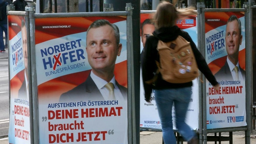 In this photo taken Tuesday, April 19, 2016 a woman walks past election posters of Norbert Hofer, candidate for presidential elections of Austria's right-wing Freedom Party, FPOE, in Vienna, Austria, Tuesday, April 19, 2016. For the first time, Austria's next president will likely be someone who is not officially backed by one of the two parties that have dominated government since the end of World War II. That reflects massive voter unhappiness _ and spells possible political turmoil ahead. (AP Photo/Ronald Zak)