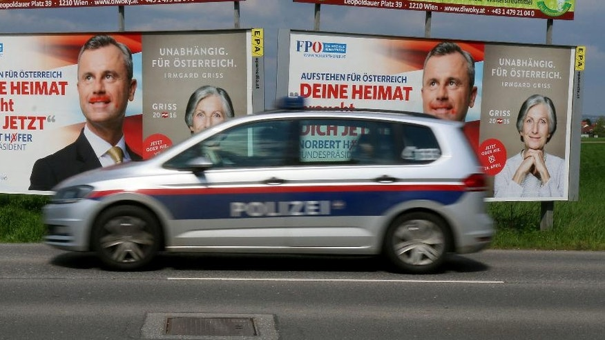 In this photo taken Tuesday, April 19, 2016 a police car drives in front of the election posters of Norbert Hofer, candidate for presidential elections of Austria's right-wing Freedom Party, FPOE, and Irmgard Griss, independent candidate, in Vienna, Austria. For the first time, Austria's next president will likely be someone who is not officially backed by one of the two parties that have dominated government since the end of World War II. That reflects massive voter unhappiness _ and spells possible political turmoil ahead. (AP Photo/Ronald Zak)