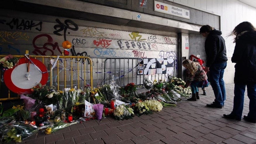FILE - In this Saturday, March 26, 2016 file photo, people stop and look at floral tributes placed outside the Maelbeek metro station, the scene of one of the bomb attacks on the Belgian capital, in Brussels. The subway station in the Belgian capital where a suicide bomber killed 16 people a month ago will reopen Monday, April 25, 2016. The Brussels regional transit authority, commonly known as the STIB, announced the reopening Friday, April 22 on social media. (AP Photo/Alastair Grant, file)
