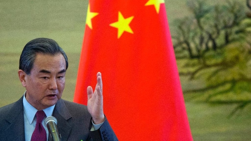 FILE - In this April 8, 2016 file photo, Chinese Foreign Minister Wang Yi gestures during a joint press conference with his German counterpart Frank-Walter Steinmeier in Beijing. Wang Yi, who is on a two day visit to Cambodia, said at a press conference in Phnom Penh, Friday, April 22, 2016 that he was delighted that Cambodia often supported Beijing's positions on world affairs. China is at odds with several of Cambodia's fellow members of the Association of Southeast Asian Nations who accuse Beijing of illegitimately extending territorial claims in the South China Sea. (AP Photo/Ng Han Guan, File)